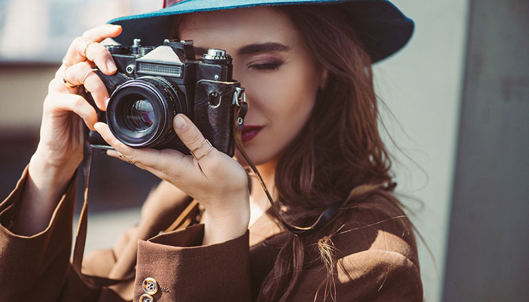woman taking photos with classic camera